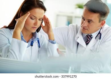 Doctor comforting his upset colleague