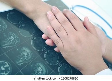 Doctor comforting patient with untreatable disease by touching his hand on the background of CT scan on the table.