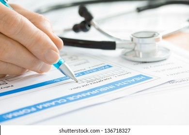 Doctor completing a Medical Insurance Claim Form by Stethoscope
