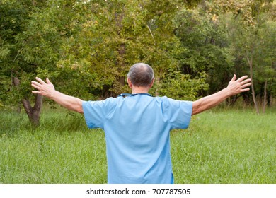 Doctor concept. The man is holding his arms wide. Freedom. Photo for your design on the background of nature. Horizontal sheet orientation
