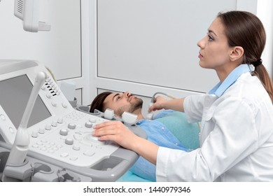 Doctor conducting ultrasound examination of patient's neck in clinic