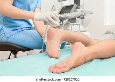 Doctor conducting ultrasound examination of patient's foot in clinic