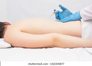 The doctor conducts plasma-lifting of the spine of a girl who has a spinal hernia, plasma therapy, medical, lumbago