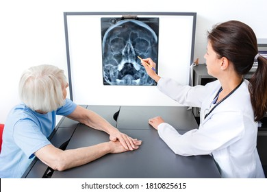 Doctor consider and discuss with senior patient X-ray of her head and maxillary sinuses. Diagnostics and treatment of sinusitis and frontal sinusitis