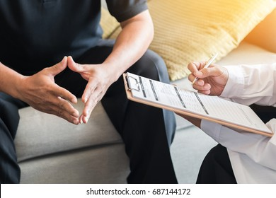 Doctor consulting male patient, working on diagnostic examination on men's health disease or mental illness, and writing on prescription record information document in clinic or hospital office