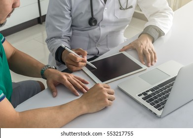 Doctor is consulting with Patient about his health on working desk which using technology tablet at hospital, physician concept