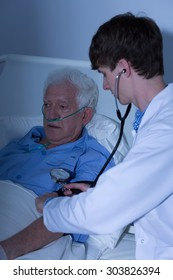Doctor controlling blood pressure of elder man