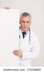 Doctor with copy space. Senior grey hair doctor in uniform looking out of copy space and smiling while isolated on white