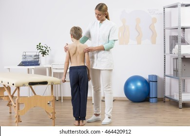 Doctor correcting small boy's body posture, standing in well equipped physiotherapist office