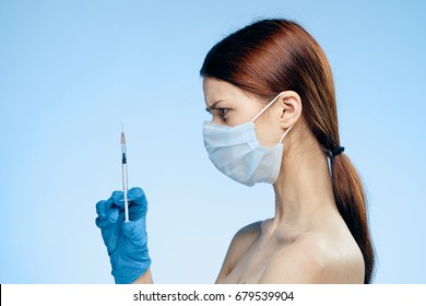 Doctor in a cosmetic mask holds a syringe on a blue background profile