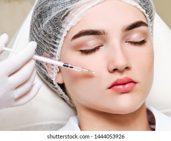 The doctor cosmetologist beautician makes the rejuvenating facial injections procedure for tightening and smoothing wrinkles on the face skin to lips of a beautiful young woman in a beauty salon