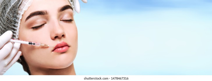 The doctor cosmetologist beautician makes the rejuvenating facial injections procedure for tightening and smoothing wrinkles on the face skin to lips of a beautiful young woman isolated