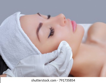 The doctor cosmetologist cleanses with a tonic the face skin of a beautiful, young woman in a beauty salon.Cosmetology skin care.