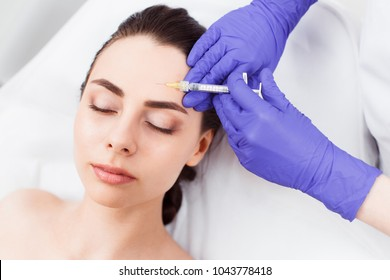 Doctor cosmetologist injects patient's face. Close up. Top view