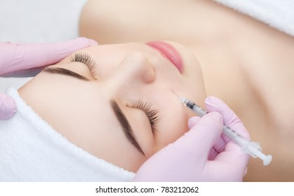 The doctor cosmetologist makes the Botulinum Toxin injection procedure for tightening and smoothing wrinkles on the face skin of a beautiful, young woman in a beauty salon.Cosmetology skin care.