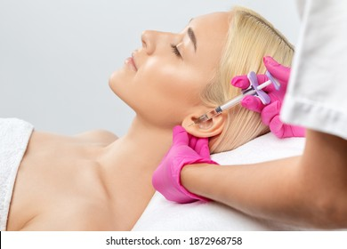 The doctor cosmetologist makes the injections procedure for smoothing wrinkles and against flabbiness of the skin on earlobe of a beautiful, young woman.Women's cosmetology in the beauty salon.
