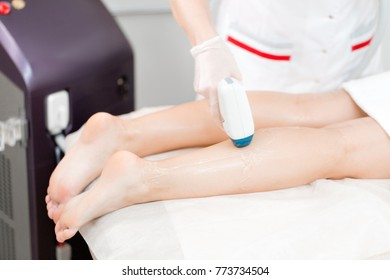 Doctor cosmetologist makes the procedure a young girl blonde. Laser epilation and cosmetology. Hair removal on ladies legs. at cosmetic beauty spa clinic.