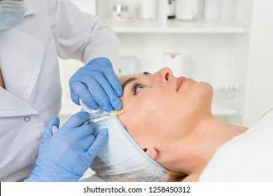 The doctor cosmetologist makes the Rejuvenating facial injections procedure for tightening and smoothing wrinkles on the face skin of a women in a beauty salon.Cosmetology skin care.