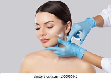 Der Kosmetologe des Arztes macht das Verfahren zur Verjüngung der Gesichtsinjektionen zur Straffung und Glättung von Falten auf der Gesichtshaut einer schönen, jungen Frau in einem Schönheitssalon.Kosmetologie Hautpflege.