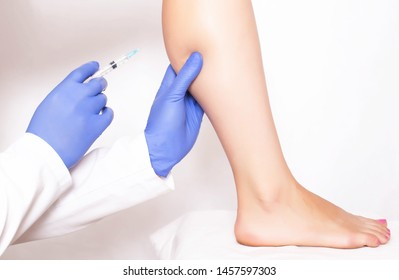 Doctor cosmetologist makes rejuvenation beauty injection to the calf muscle on the leg of the girl. Rejuvenation with injections of Hilauri acid, medical