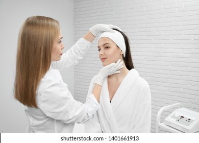 Doctor cosmetologist in white coat and white medical rubber gloves inspecting face of patient. Young woman in white bathrobe standing and looking away. Concept of care.