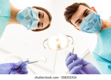 Doctor and dentist assistant, protection gloves, using dental tools, a mask looking at the camera. Close-up