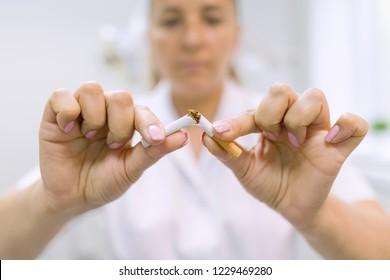 Doctor dentist breaks a cigarette, broken cigarette close up, background dental office. Stop Smoking.