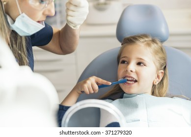 Doctor dentist teaching a child to brush teeth. Dentist concept.
