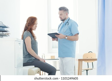 Doctor diagnosing a female patient with headache in a hospital