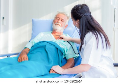 The doctor is diagnosing the patient on the bed of hospital.
