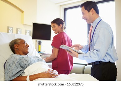 Doctor With Digital Tablet Talks To Woman In Hospital Bed