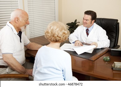 Doctor discussing treatment options with an elderly couple in his office.