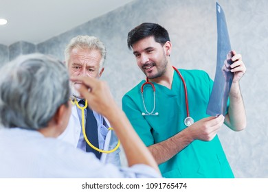 doctor discussing x-ray with Asian senior man in hospital