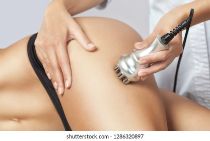 The doctor does the Rf lifting procedure on the legs and hips of a woman in a beauty parlor. Treatment of overweight and flabby skin.