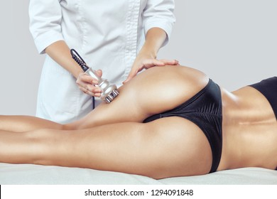 The doctor does the Rf lifting procedure on the legs, buttocks, thighs and hips of a woman in a beauty parlor. Treatment of overweight and flabby skin.
