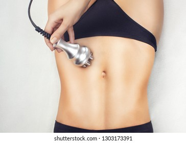 The doctor does the Rf lifting procedure on the stomach and hips of a woman in a beauty parlor. Treatment of overweight and flabby skin.
