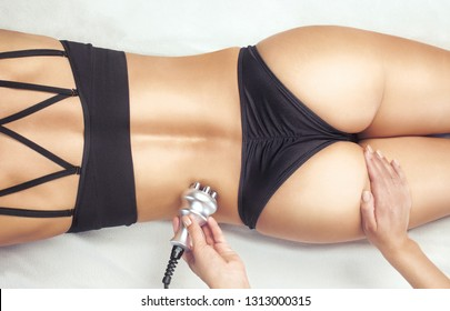 The doctor does the Rf lifting procedure on the legs, buttocks, hips and lower back of a woman in a beauty parlor. Treatment of overweight and flabby skin.