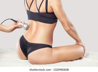 The doctor does the Rf lifting procedure on the buttocks, hips and lower back of a woman in a beauty parlor. Treatment of overweight and flabby skin.