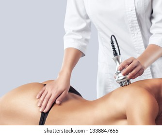 The doctor does the Rf lifting procedure on the back and shoulder blades of a woman in a beauty parlor. Treatment of overweight and flabby skin.