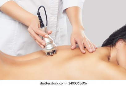 The doctor does the Rf lifting procedure on the back of a woman in a beauty parlor. Treatment of overweight and flabby skin.