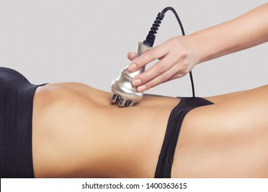 The doctor does the Rf lifting procedure on the abdomen and hips of a woman in a beauty parlor. Treatment of overweight and flabby skin.