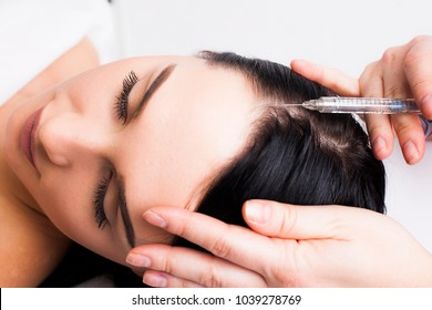Doctor doing botox head of a young brunette woman