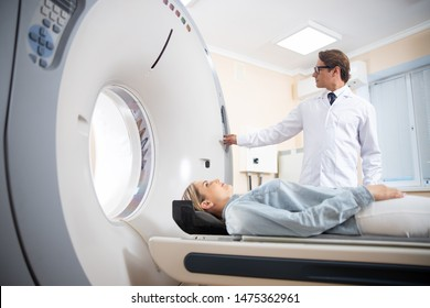 Doctor doing computed tomography for female patient stock photo. Medicine diagnostic concept