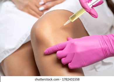 Doctor doing stem cell therapy on a patient's knee after the injury. Treating knee pain with platelet-rich plasma injection. Treatment of arthritis and osteoarthritis.Medical and cosmetology concept.