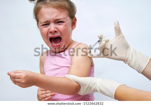 Doctor doing vaccine injection to crying girl on a white background