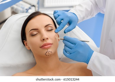Doctor drawing correction marks on calm woman