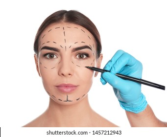 Doctor drawing marks on woman's face for cosmetic surgery operation against white background