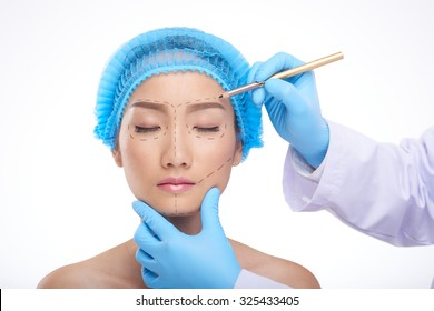 Doctor drawing perforation lines on face of patient before surgery