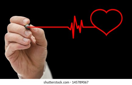 Doctor drawing shape of a heart beating cardiograph. Isolated over black background.