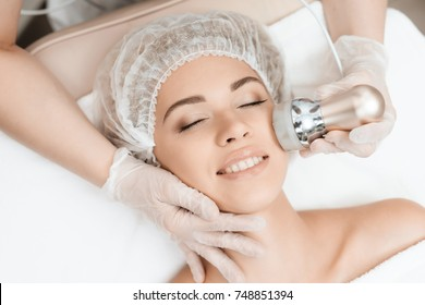 The doctor drives the girl in the face of the photoepilator. The girl came to the procedure for laser hair removal. She lies on the couch and smiles.